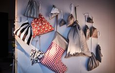 Muitos tamanhos diferentes de sacos para prendas de Natal pendurados numa parede.
