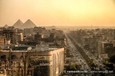 The view from the top of the hotel wasn't inspiring. The daily smog of the Egyptian traffic lay over the city, blurring the hectic life that existed beneath it. Through the haze, off in the distance next to the golden glow of the setting sun was the discernible shape; The Pyramids of Giza.