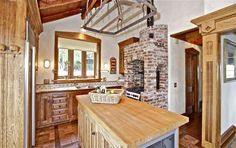 A raised, wood-burning brick fireplace warms the kitchen, and a wine refrigerator built into the center island lends utilitarian flair to the room.