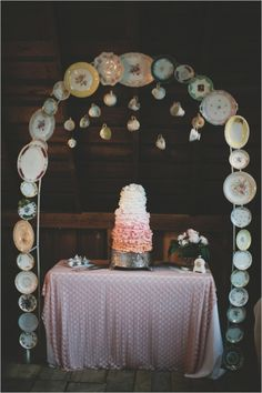 A cake table arch made from mix and match china plates and cups.