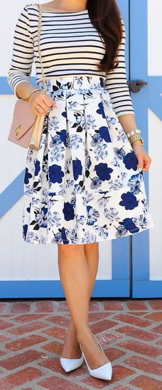 Black and white striped shirt, 3/4 length sleeves, knee length blue floral structured skirt