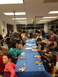 Children and their parents enjoying Hanukkah snacks at Hanukkah party 2013.