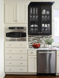 Add drama to your kitchen with a cabinet makeover. This space contrasts light-color cabinetry with a dark-stained cabinet. The glass front on the espresso cabinets keeps the section from feeling heavy and is a chic way to display glassware. The mix of cab Ugly Kitchen, Kitchen On A Budget, Kitchen Decor, Kitchen White, Country Kitchen, Kitchen Storage, Kitchen Ideas, Dad's Kitchen, Cheap Kitchen