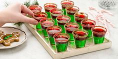 Grinch Jell-o Shots LIME-SUGAR RIM 2 tbsp. lime juice 1/4 c. Red and green sanding sugar LIME JELL-O LAYER 1 c. water 1 packet lime Jell-o mix (3 ounces) 4 oz. vodka (or tequila), chilled STRAWBERRY JELL-O LAYER 2 c. water, divided (place 1 c. in fridge to chill) 1 packet strawberry Jell-o mix