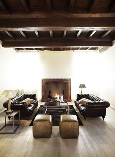 Masculine Room with Brown Leather Chesterfield Sofas, exposed Dark Wood Beams, and Rustic Fireplace.