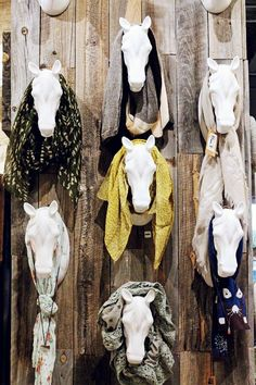 Horse heads secured to a wall are used to grab attention and display scarves. Could be used in a craft fair booth.