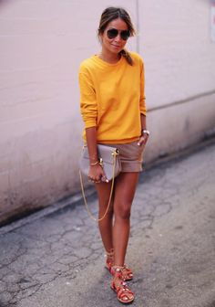 Bright sweatshirt over khaki shorts with strappy sandals and clutch bag