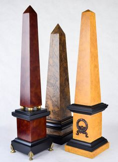 A trio of painted decorative obelisks made of wood. The group includes a gold, light brown, and red brown obelisk, all with faux marbled paint. The obelisks all have squared pedestal bases. The gold obelisk has a decorative metal wreath on the base, and the red brown obelisk has gilded spheres and feet.