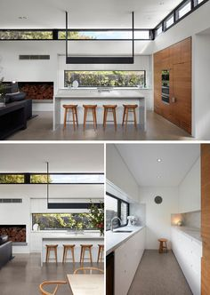 In this modern white kitchen, a window with views of the garden has been used as a backsplash, while hidden behind a wooden door at the end of the counter opens to reveal a hidden walk-in pantry with plenty of storage. #ModernKitchen #WhiteKitchen #WalkInPantry #Pantry