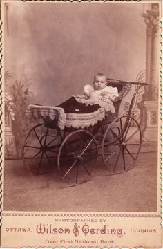 This scalloped edged cabinet card captures a baby sitting in a carriage in the studio of J. A. Wilson &  August F. Gerding, in Ottawa, Illinois. The attentive baby seems to be intensely surveying the studio. A blanket sits neatly atop the carriage
