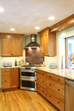 Cherry Wood Kitchen- corner stove and corner sink, stainless steel appliances, tile back splash, mail sorting area, granite countertops, natural cherry cabinets