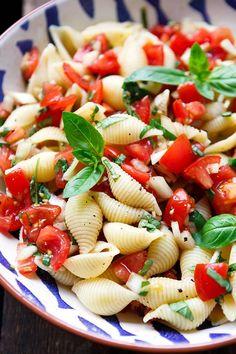 Bruschetta Nudelsalat mit saftigen Tomatenwürfeln, Basilikum, Knoblauch, Zwiebel, Nudeln, Olivenöl und Balsamico. Perfekt zum Grillen und Picknicken.