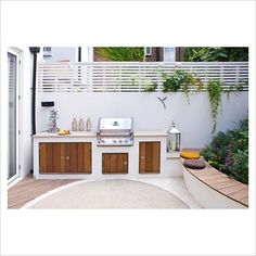 Small patio garden with raised bed and built in outdoor kitchen and barbecue.