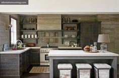 The kitchen cabinets, by Michael Bell of Bell Custom Cabinetry, are a fusion of American and European sensibilities. Knotty pine walls and a pecan wood island were both treated with a lime wash by San Marco Paint USA. Antiqued limestone countertops, Atlanta Kitchen Inc. Thermador appliances, Guy T. Gunter  Associates. Brizo faucet, available through PDI. Vintage sconce, barstools and accessories, Bungalow Classic. Rug, Keivan Woven Arts. Other  accessories, A. Tyner Antiques.