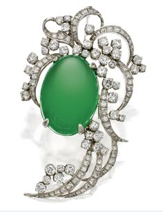 Platinum, jadeite and diamond pendant brooch. Set in the center with an oval jadeite measuring approximately 23.5 by 17.6 mm., framed by a ribbon and foliate motif set with round diamonds weighing approximately 5.20 carats.