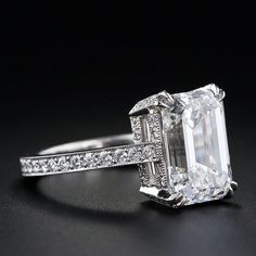 set in a millegrained ring that is completely outlined by eighty-eight shimmering round brilliant cut diamonds.