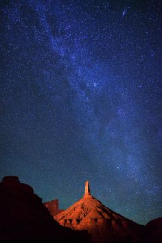 Milky Way over the light-painted Castle Rock, a sandstone monument in Castle Valley, Utah