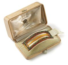 A Jeweled and Guilloché Enameled Tortoiseshell Hair Clip By Fabergé, apparently unmarked, circa 1903. Rectangular, the border mounted at intervals with diamond-set flowerheads issuing leaves enameled in translucent green over a guilloché ground, in original silk lined wood case stamped 'Fabergé St. Petersburg, Moscow, London'