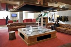 modern but inviting office space, tufted couch, red rug, large coffee table