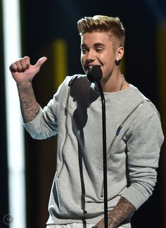 July 27 : Justin onstage after accepting his Champ of Charity award from Cody Simpson at the 2014 Young Hollywood Awards.