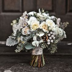 Winter wedding bouquet of mini cymbidium orchids, silver brunia, juniper, pine boughs, anemones, pine cones, garden spray roses, seeded eucalyptus, Vendela roses, and dusty miller