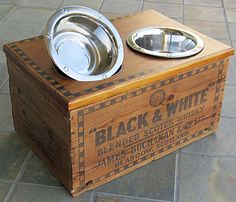 Unique eco-friendly repurposed genuine vintage Black & White Scotch Whisky from Glasgow Scotland crate dog feeding station. Elevate your dog's food and water source to minimize joint stress and keep their food and water off the floor. This Black & White Scottish crate has been recycled into a stylish dog feeder with storage, too. Barking good one of a kind gift for your favorite dog.