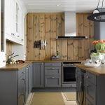 Vinkelkjøkken malt i heldekkende grått (Sort Pepper), med gråpatinert benkeplate i eik. Kjøkkenet har en minimalistisk fremtoning, der mye av oppbevaringsfunksjonene er lagt til store skuffer. En a…