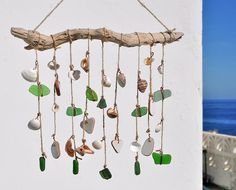 I made this suncatcher using a genuine branch of weathered driftwood, authentic sea glass wire wrapped in copper wire, genuine seashells