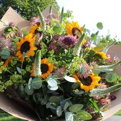 Rustic hand tied bouquet in bold shades featuring sunflowers
