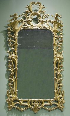 "A George III Carved Giltwood Mirror,     CIRCA 1765,     Height: 88"" Width: 44"".         The rectangular plate enclosed by stylized architectural elements issuing elaborate floral and foliate swags and supporting finely carved Ho-Ho- birds, flanking the pierced acanthus carved cresting; the apron with a conforming cartouche hung with foliate swags."