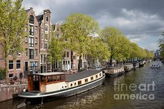 Houseboats barges and apartment buildings on a canal in the city of Amsterdam, Netherlands.
