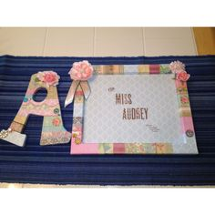 Covered picture frame and initial with scrapbook paper, modge podge, ribbons and flowers