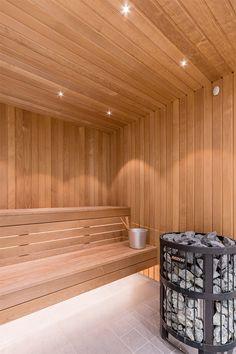 Väggar i vitt kakel med glansig yta och golv i grå klinker. En vägg i det stora badrummet täcks av natursten och förstärker spakänslan. Duschen är snarare ett duschrum, med en vägg i glas och en väldig takdusch. Också den stora bastun har en vägg helt i glas. I en avskild del av badrummet finns en vägghängd toalett och ett vägghängt handfat med en underdel i ljust trä. Home Spa Room, Spa Rooms, Sauna Lights, Portable Sauna, Sauna Design, Finnish Sauna, Steam Sauna, Backyard Pavilion, Sauna Room