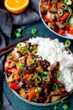 Two bowls of crispy orange beef with rice. Topped with spring onions.