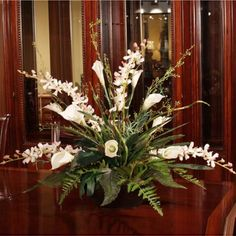 """Calla Lily and Silk Orchid Arrangement AR208-96. If you love calla lilies, this silk floral arrangement is a must have.  Beautiful silk calla lilies and white orchids are blended with seeded berry branches and complementary greenery for a striking centerpiece.  Set in a powdered black contemporary metal container. Measures 26""""H X 24""""W"""