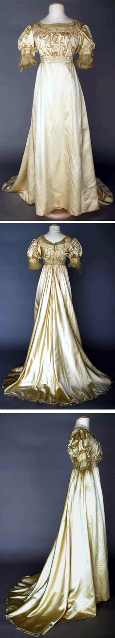"""Evening gown ca. 1905-10. Candlelight satin Empire trained gown, square neckline, short puffed sleeves, bands of stylized cream embroidery, neckline & sleeves with gathered silk chiffon trim. Augusta Auctions called the style """"esthetic,"""" but I think it's just an elegant example of a Regency- or Empire-style gown."""