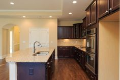 Kitchen with island, granite countertops, staggered cabinets and stainless steel appliances in the Salerno
