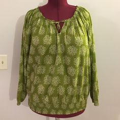 "Merona Lightweight Green Floral Print Boho Top Up for grabs is this top from Merona. It is a plus size 2 (equivalent to a size 20W / 22W ) and measures 28"" from shoulder to hem and has a 52"" bust, and a 42"" bottom hem unstretched and a 78.5"" bottom hem stretched. This blouse is a boho style with a flowy fit and a drawstring tie neckline. It has a cream floral print on a moss green background. This shirt has been gently worn and is in fantastic condition. Merona Tops Blouses"