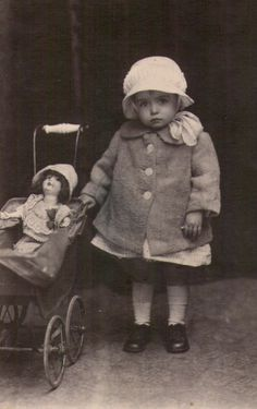 Vintage / antique photo of little girl with her doll in pram.