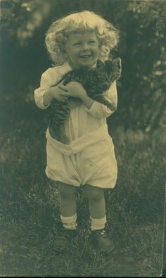 Full-length portrait of a child, standing, facing front, holding a kitten, location unknown, undated | Mary H. Northend photographic collection, 1904-1926 (PC034) -- Historic New England