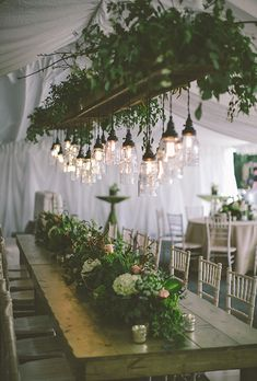 Brides.com: . To create an intimate vibe, this couple opted for low-hanging edison bulbs strung from a floral chandelier, a cool urban touch against the floral décor.