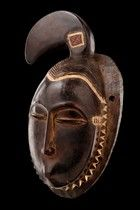 "Yaure face mask - the beak-like projection on top reminding of a hornbill which is why the mask can be assigned to the ""lomane"" mask type of the ""je"" group. ""Lomane"" is a derivation of the word ""anoman"", which means ""bird"" in the Baule language. ""Lomane"" masks were danced at funerary ceremonies, the dancer bending over the deceased and touching him. According to the assertion that the mask destroys the worms, decomposing the body, this act is equivalent to a kind of symbolic purification…"