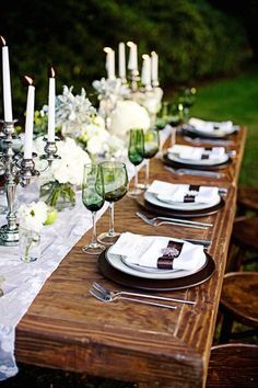 Rustic table, silver candlesticks with white candles, white runner and white flowers.