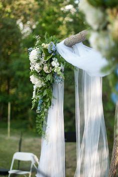 a rustic tree alter is decorated with white tule and pretty swags of fresh blooms - thereddirtbride.com - see more of this wedding here