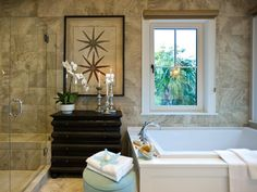 HGTV.com showcases the elegant master bathroom at HGTV Dream Home 2013, which  features a glass-enclosed shower, soaking tub and vintage-style storage dresser.