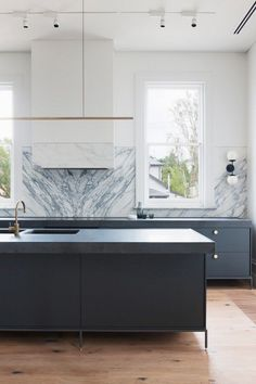 Modern kitchen with marble backsplash, a gold pendant light and blue cabinents