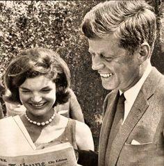 JFK & Jackie laughing at their newspaper coverage.