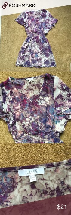 """Delia's Sheer Flounce Sleeve Multi Color Dress XS Delias Sheer Flounce Sleeve Multi Color Dress XS Color: Abstract print with various shades of purple, blue, pink, grey and cream Size: XS (would also fit girls 14/16) Fabric Content: 100% Polyester Features/Details: Flounce sleeves, sheer overlay, stretch waist, v-neck Condition: Excellent used condition. A few loose threads.  Approximate measurements (may be slightly off): Armpit to armpit: 17"""" Waist: 10.25"""" Bottom hem width: 23.5"""" Total…"""
