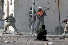 Forças do novo regime da Líbia combatem tropas de Gadaffi em Sirte, enquanto um dos seus companheiros toca um violão no meio do conflito, em 2011.