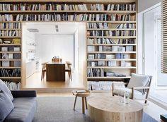 Un salon avec une maxi bibliothèque sur-mesure ouverte sur la cuisine